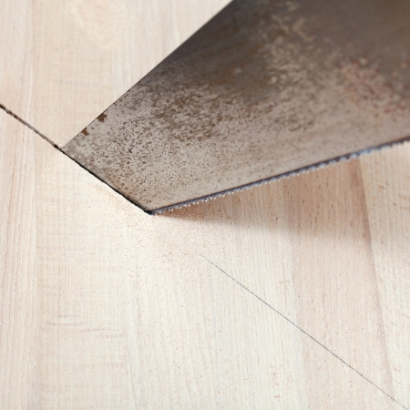 wooden board is cut with hacksaw close up photo