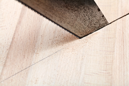 wooden plank is cut with hacksaw close up photo