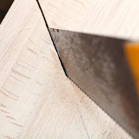 hacksaw: wooden plank is cut with hacksaw close up