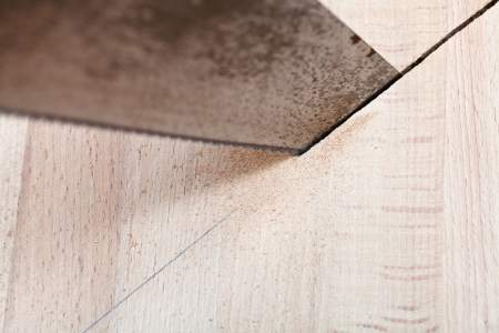 hacksaw: wood board is cut with hacksaw close up Stock Photo