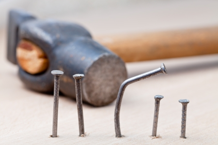 hammer, line of nails and curved nail in wooden board