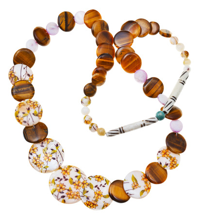 round collar: top view of necklace from natural mineral beads of decorated nacre, tigers eye stones, carved bone isolated on white background