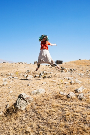 prehistoria: ni�a saltando sobre Zorats Karer (Carahunge) plateau - prehistoria monumento megal�tico en Armenia