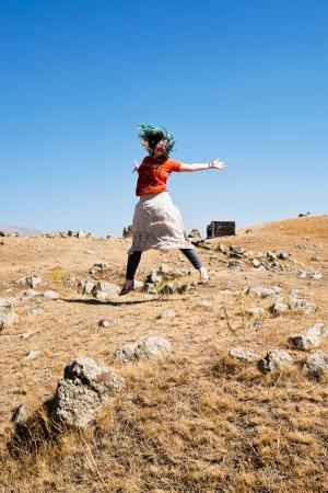 prehistoria: Mujer joven saltando en Zorats Karer (Carahunge) plateau - prehistoria monumento megal�tico en Armenia