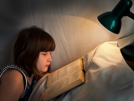 girls night: teen girl reading book on bed at night by light of lamp on bed Stock Photo