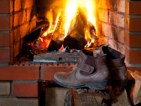 hotbed: boots are dried near fire in fireplace in evening time