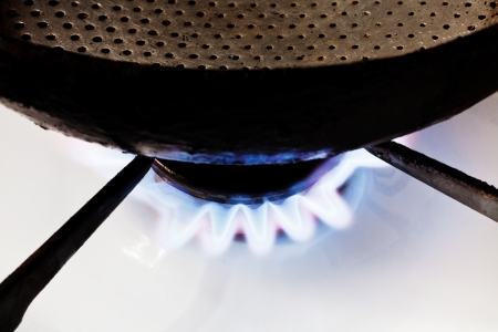 normative: frying pan on burning gas in hearth ring of kitchen stove