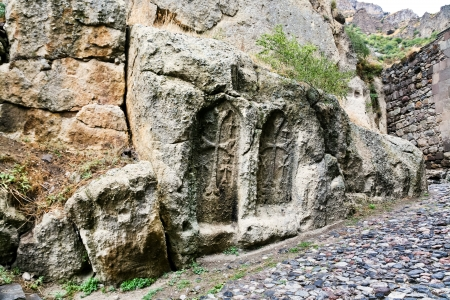 geghard: carved cross on ancient stone wall of medieval geghard monastery in Armenia