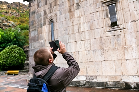 geghard: tourist shooting landmark by smartphone - Katoghiken church of medieval geghard monastery in Armenia Stock Photo