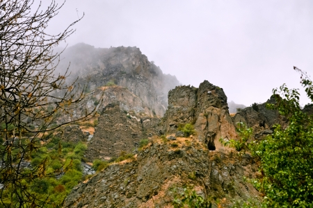 geghard: Cliff with cave near Geghard monastery in Armenia in rain. Cliffs surrounding Geghard monastery and Azat river