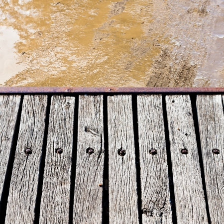 wooden footbridge over slushy rural road photo