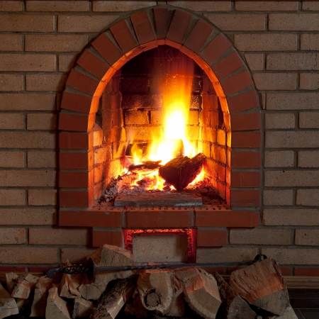 firebox: poker, firewood and flames of fire in fireplace in evening time
