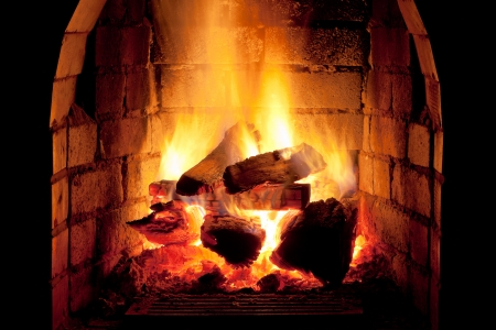 stone fireplace: flames of fire in fireplace in evening time Stock Photo