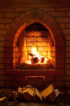 火かき棒、薪、夜の時間で暖炉の火の炎 写真素材