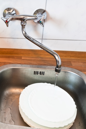 washing-up in metal washbasin in kitchen photo