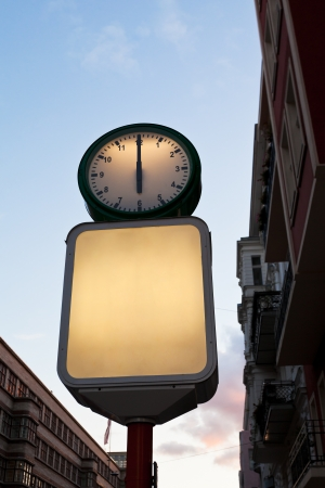 illuminated round street clock and blank advertising billboard in evening photo