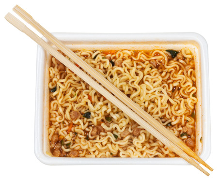 instant ramen: top view of cooked instant ramen and wooden chopsticks in foam cap isolated on white background