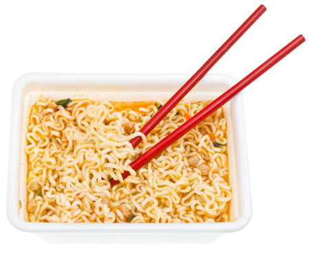 instantnudeln: eating of cooked instant noodles by red chopsticks from foam cap isolated on white background