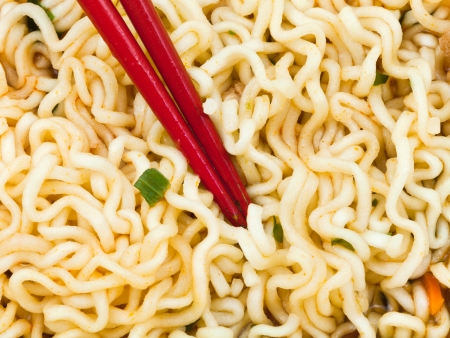instant ramen: eating of cooked instant ramen by red chopsticks close up
