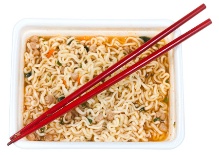 top view of cooked instant noodles and red chopsticks in foam cap isolated on white background photo