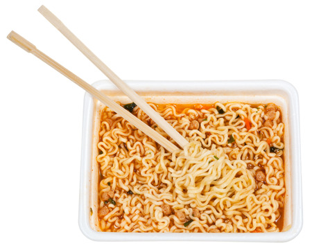 glutamate: eating of prepared instant noodles by wooden chopsticks from foam cap isolated on white background