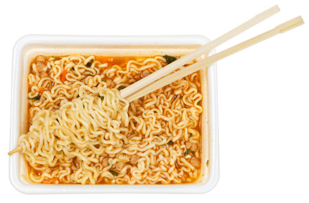 instant ramen: eating of prepared instant ramen by wooden chopsticks from foam cap isolated on white background