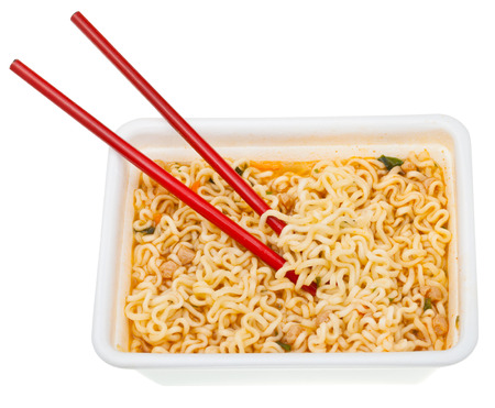 instant ramen: eating of cooked instant ramen by red chopsticks from foam cap isolated on white background Stock Photo