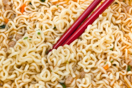 instantnudeln: eating of cooked instant noodles by red chopsticks close up