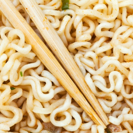 instant ramen: eating of cooked instant ramen by wooden chopsticks close up Stock Photo