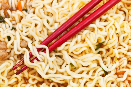 instant ramen: red chopsticks on cooked instant ramen close up
