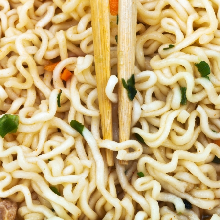 instant ramen: wooden chopsticks on cooked instant ramen close up Stock Photo