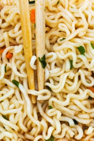 wooden chopsticks on cooked instant noodles close up photo