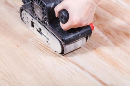 afwerking ashwood oppervlak met de hand-held bandschuurmachine Stockfoto