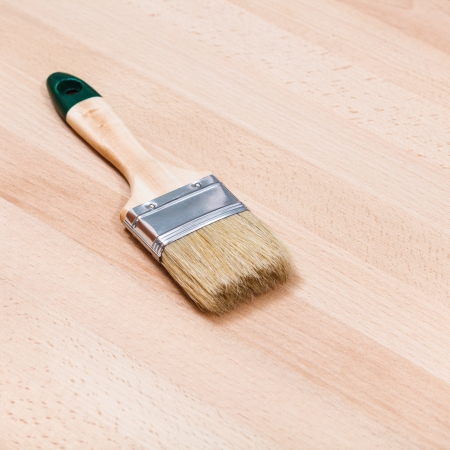 new paint brush on beech wooden board photo