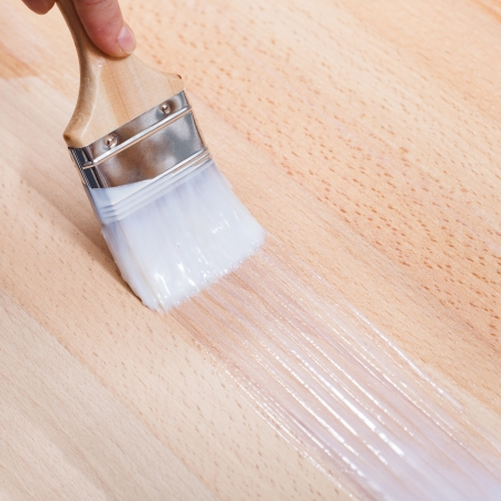 putting layer of clear lacquer on surface of beech top table by paint brush