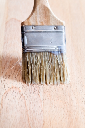 lacquering of beach wooden surface by paint brush photo