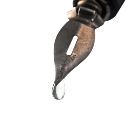 libel: transparent fluid drop dripping from the tip of pen close up Stock Photo