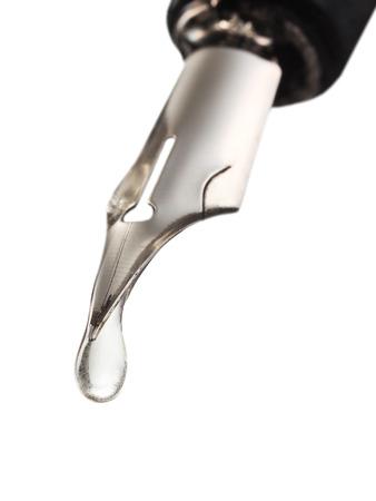libel: transparent fluid drop dripping from the nib of pen close up Stock Photo