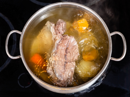 seasoning: open pan with cooking beef broth with with seasoning vegetables