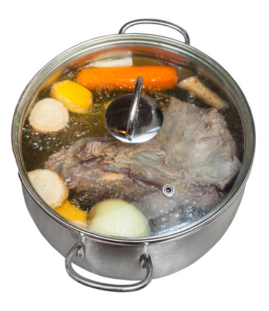 boiling of beef broth with seasoning vegetables in steel pan isolated on white background photo