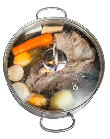 simmer of beef broth with seasoning vegetables in steel pan isolated on white background photo