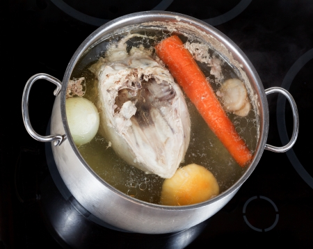 boiling of chicken broth with seasoning vegetables in steel pan on glass ceramic cooker photo