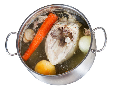 boiling of chicken broth with seasoning vegetables in steel pan isolated on white background photo