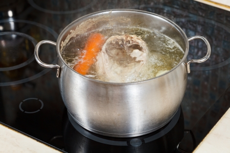 simmering chicken soup with seasoning vegetables in steel pot on glass ceramic cooker