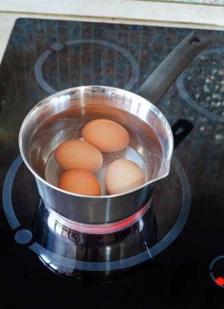 Chicken eggs are cooked in metal pot on electric stove in kitchen Stok Fotoğraf