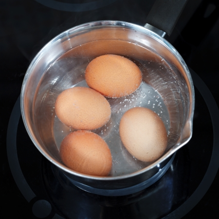 top view of boiling chicken eggs in metal pot on electric stove in kitchen Banque d'images