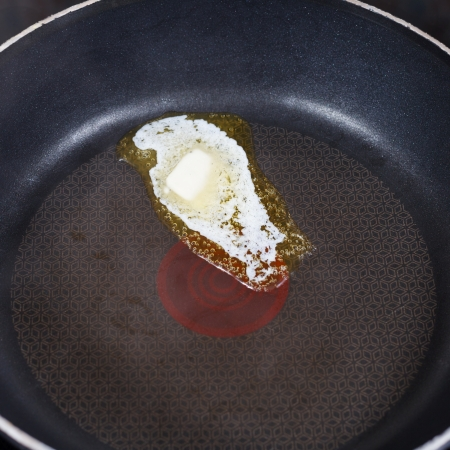 small piece dairy butter melting on hot frying pan close up photo