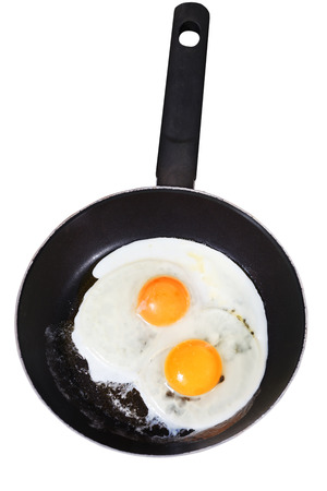 two fried eggs in frying pan isolated on white background photo