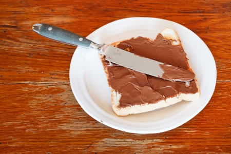 sweet sandwich from fresh toast with chocolate spread on white plate, table knife on wooden table photo