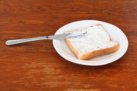 sandwich from toast and cottage cheese with herbs on white plate, table knife on wooden table photo